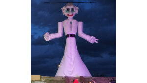 Nighttime photo of giant Zozobra marionette with people in the foreground